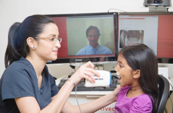 In this photo from Livecare, a specially trained medical assistant uses an exam camera to capture images of a patient's throat while a doctor (on screen in the background) observes remotely. Photograph by: Mercedes Leung