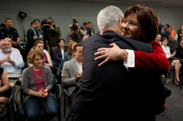 British Columbia Premier Christy Clark, right, embraces Dr. Julio Montaner, director for the B.C. Centre for Excellence in HIV/AIDS, after announcing the dedicated AIDS ward at St. Paul's Hospital would no longer just treat patients with HIV/AIDS because of a lack of demand due to the success of the centre, during a news conference in Vancouver, B.C., on Tuesday May 27, 2014.